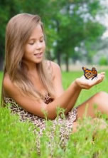 Young lady releasing monarch butterfly.